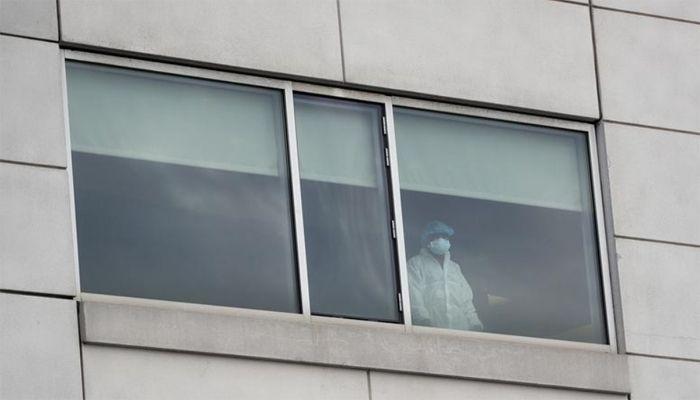 ব্রুকলিনের মাইমনিডেস মেডিকেল সেন্টারের জানালা দিয়ে তাকিয়ে আছেন এক স্বাস্থ্যকর্মী। ছবি: রয়টার্স